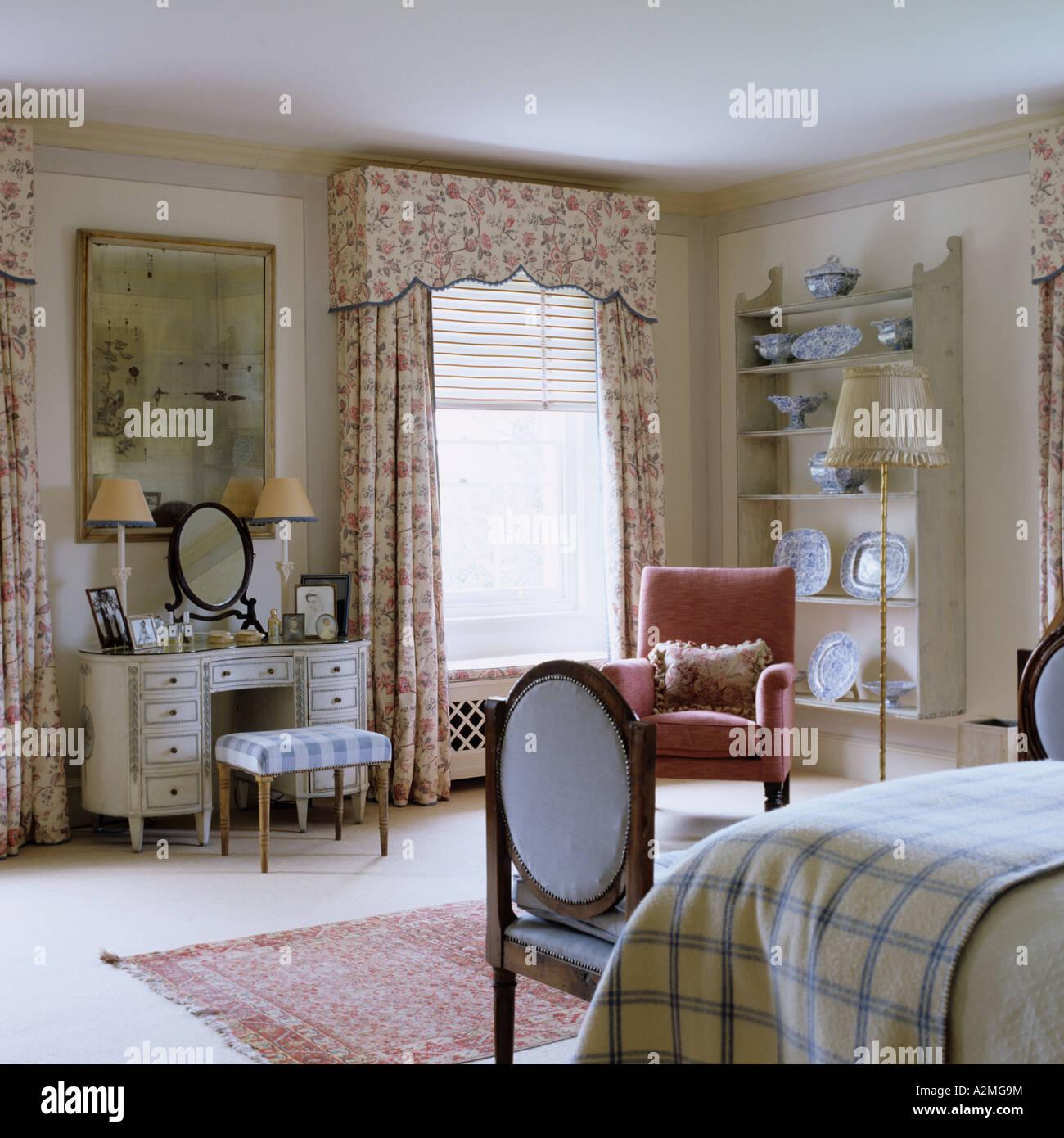 dormitorio con cortinas estampadas y tocador en la casa de