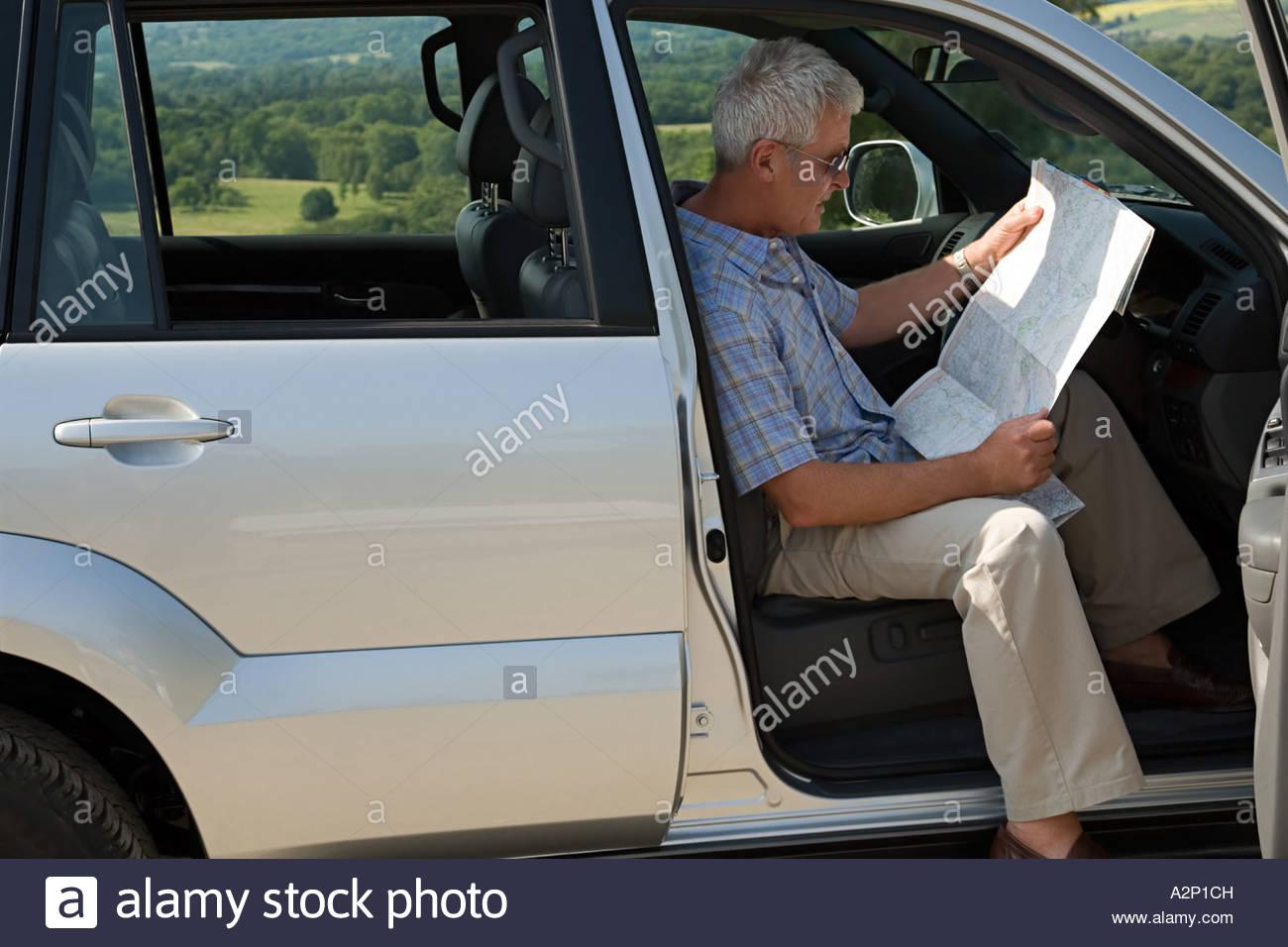 El hombre en el coche con el mapa Imagen De Stock