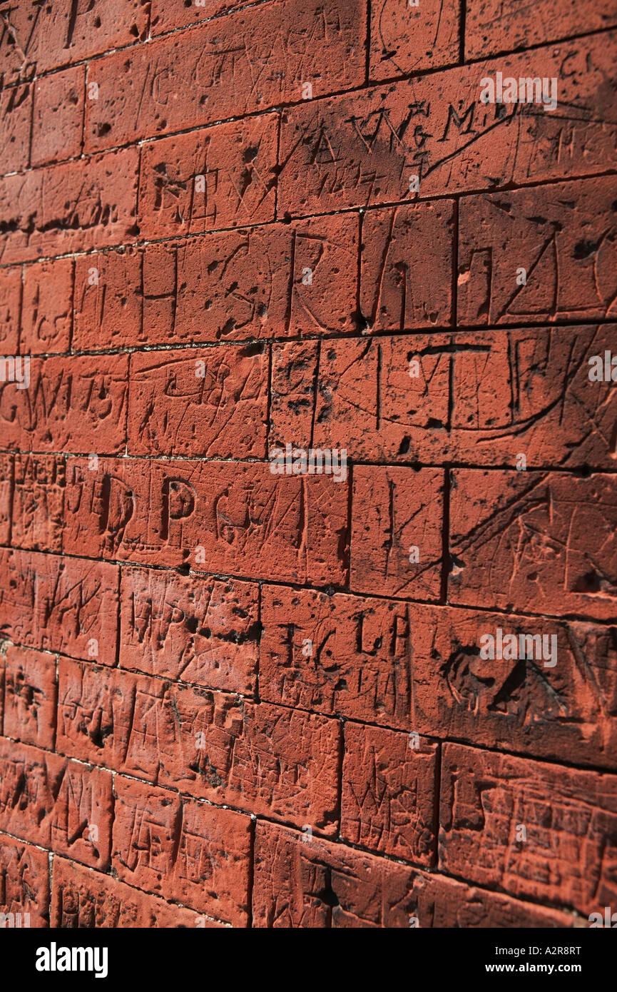 Graffiti quiso en mampostería en muros de la vieja escuela Dedham North Essex UK Imagen De Stock