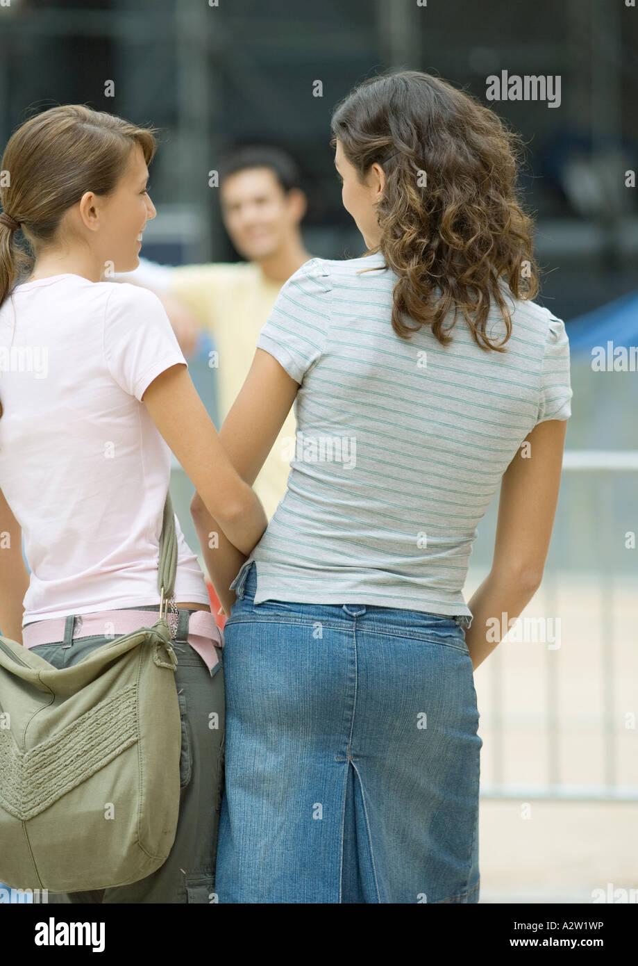 Las adolescentes enfrentan los adolescentes varones, vista trasera Imagen De Stock