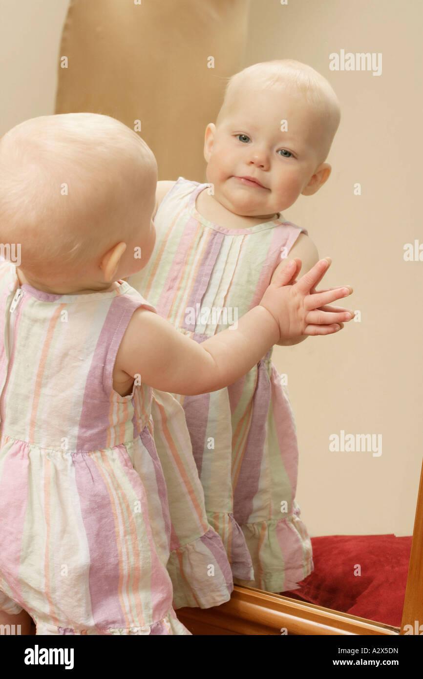 Bebé hembra disfrutando de ella, como ella misma afirma mirando en un espejo. Foto de stock
