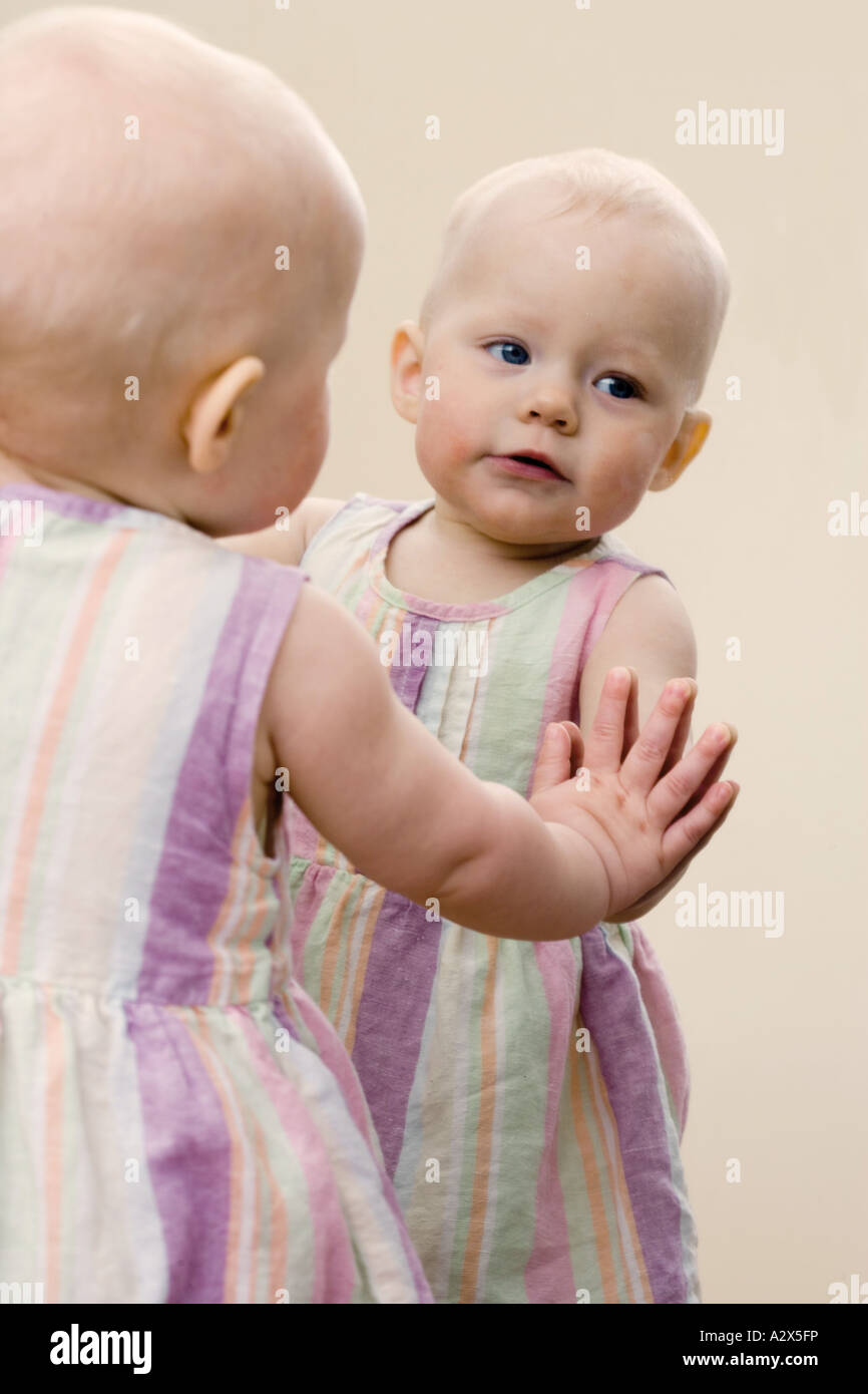 8 mes de edad niña reconoce a sí misma como se ve en un espejo. Foto de stock