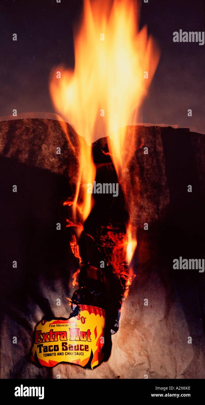 La comida mexicana 'Still life' concepto de comercialización. Flaming hot salsa Taco etiqueta en el fuego. Imagen De Stock