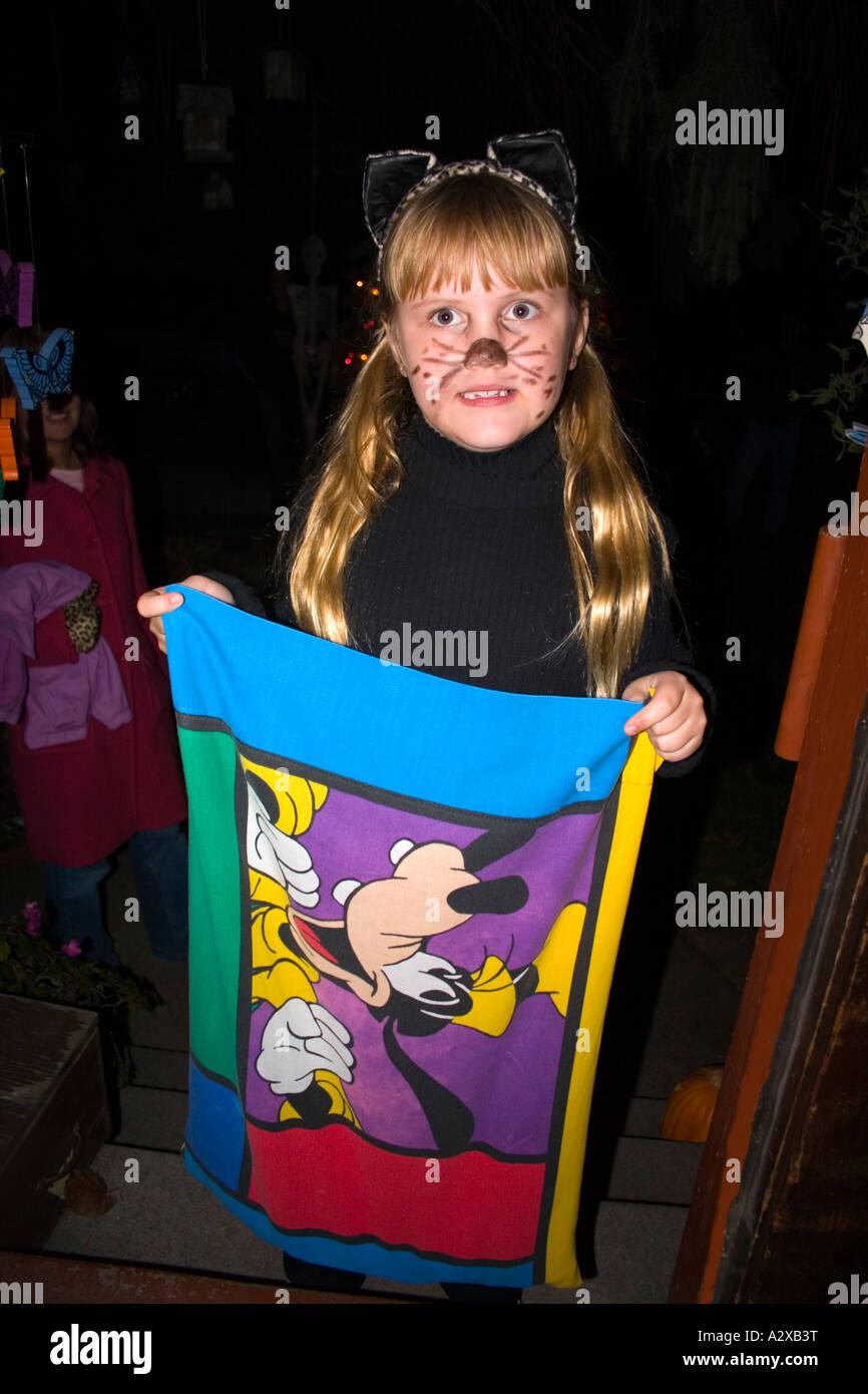 Halloween trick or treater en un traje de gato con Walt Disney Goofy bolsa colectora de 8 años de edad. St Paul Minnesota, EE.UU. Foto de stock