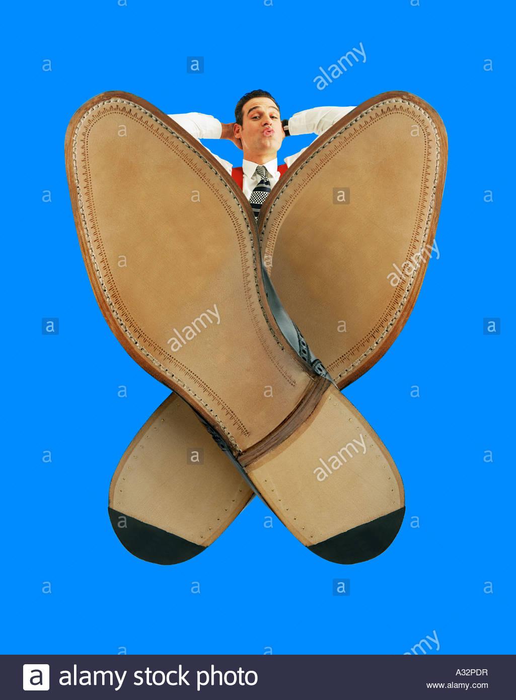 Hombre de aspecto relajado con sus pies sobre el escritorio, cruzaron la frontera. Efecto de gran angular extremo. Imagen De Stock
