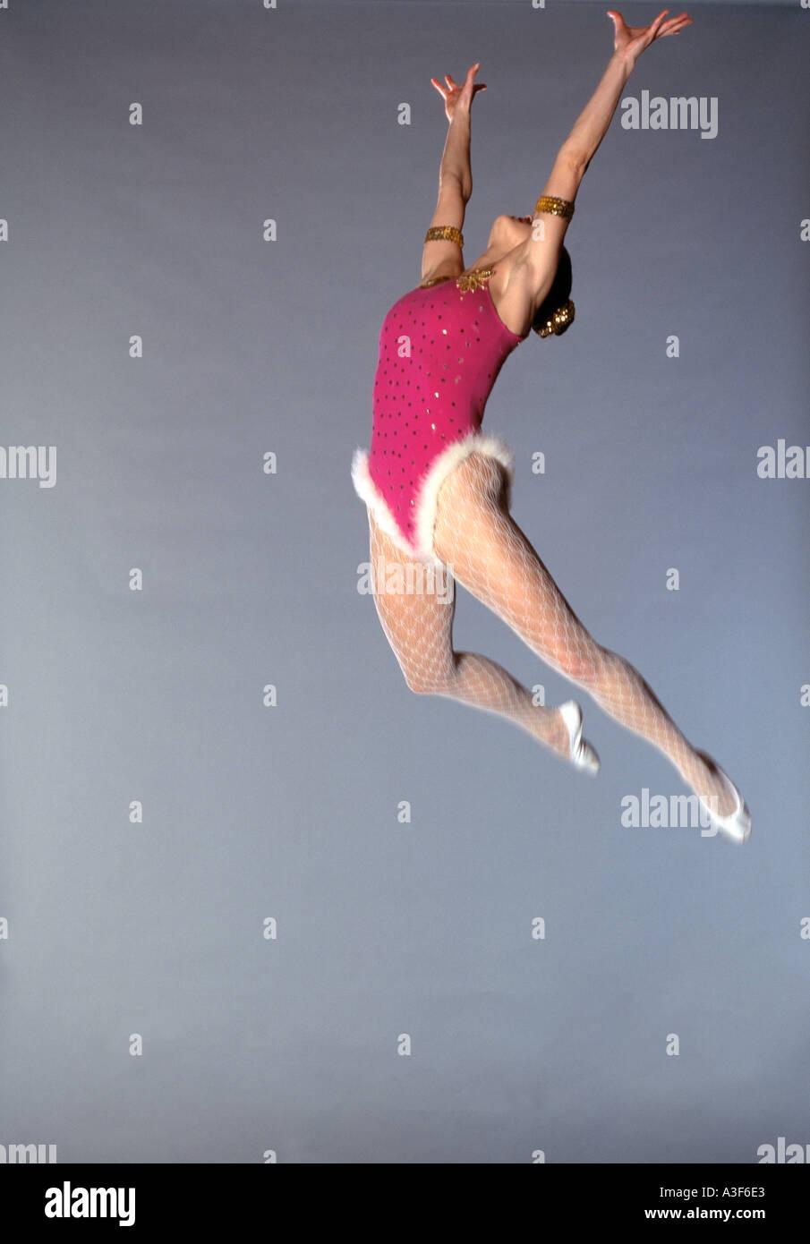 Trapecista volando por el aire fondo gris Foto de stock
