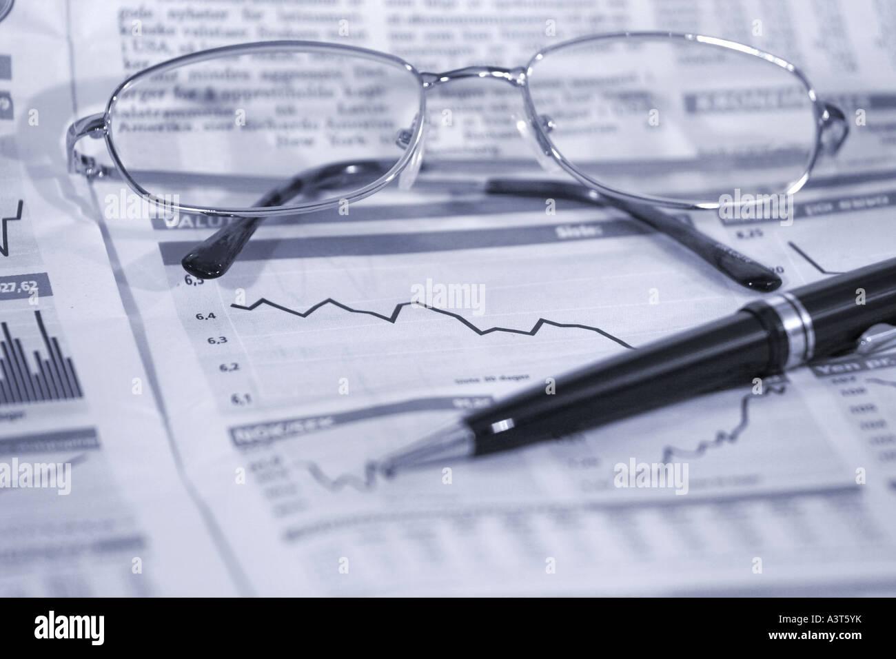 Gafas y bolígrafo encima de cifras financieras con el precio de las acciones Foto de stock