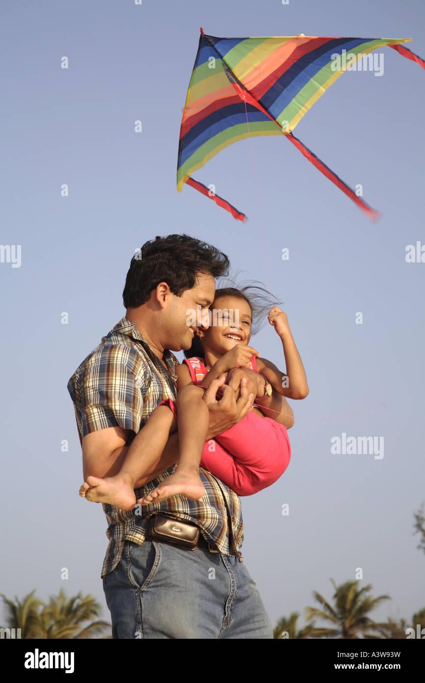 Padre e hija divirtiéndose en volar una cometa de picnic en la playa disfrutando de sol, la arena y el mar Imagen De Stock