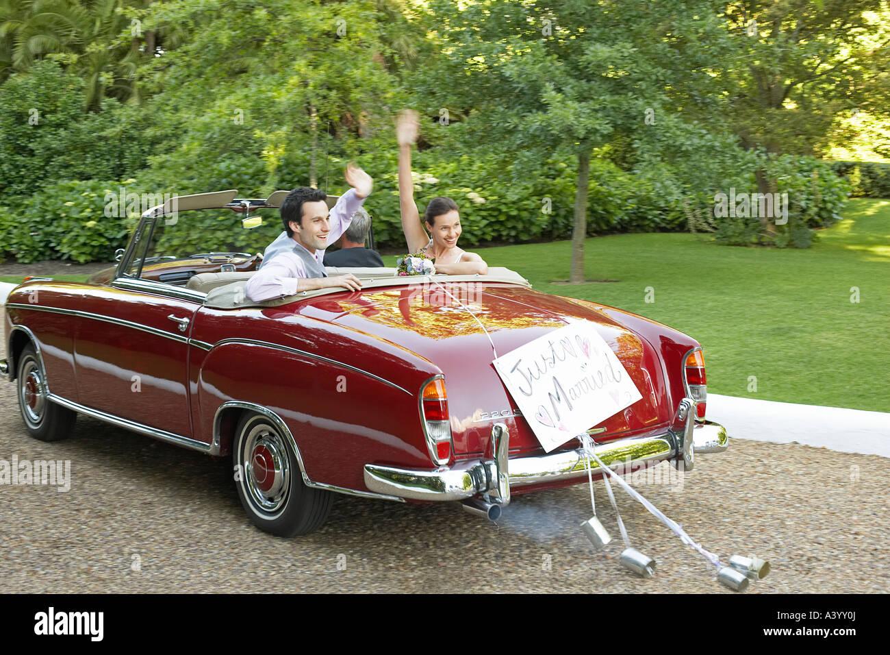 La novia y el novio adulto medio en coches de época, agitando las manos Imagen De Stock