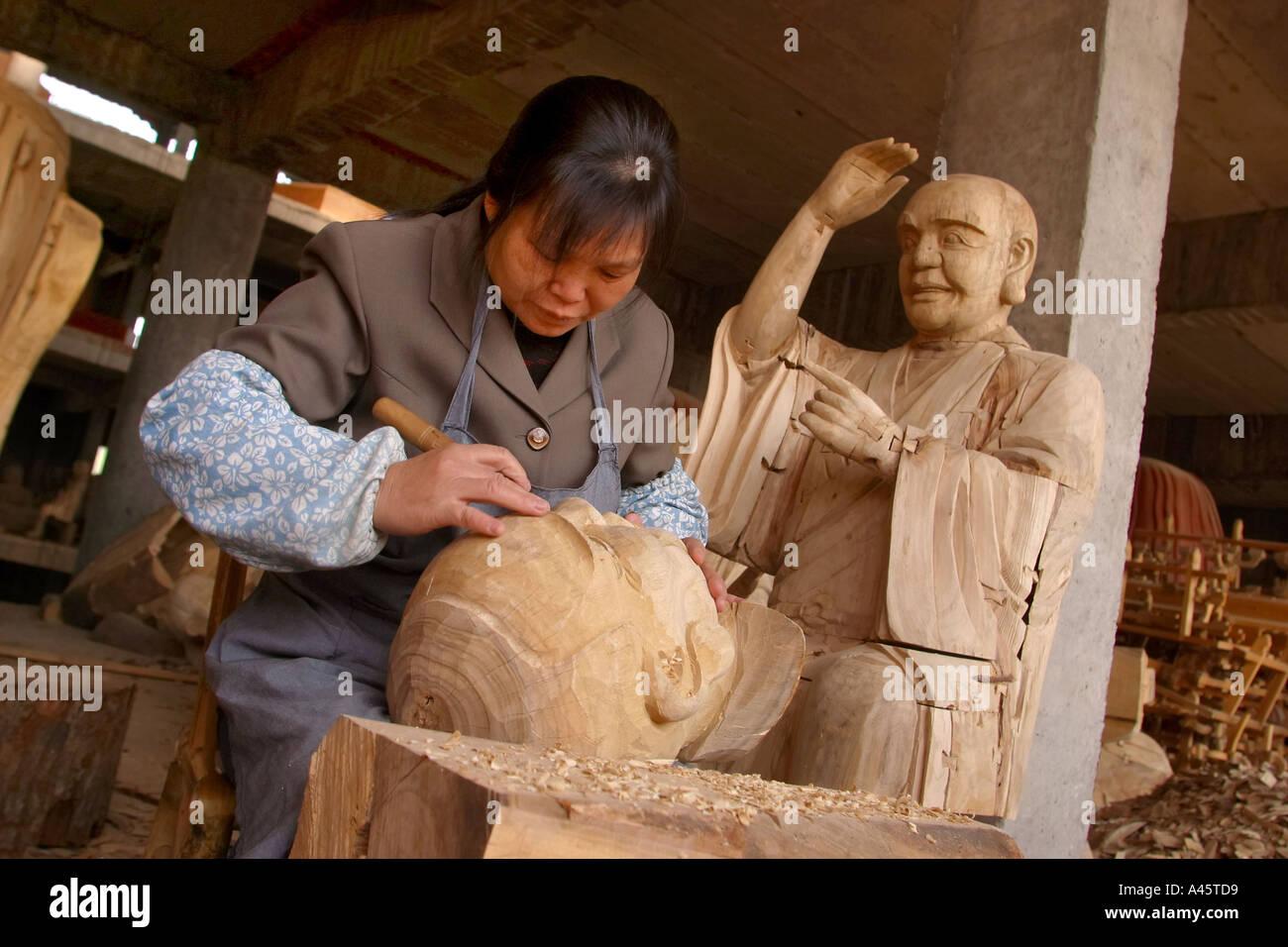eafbd35849c Una mujer trabajadora que se atribuían una cabeza de madera en la ciudad  budista una fábrica de estatuas religiosas en China tiantai