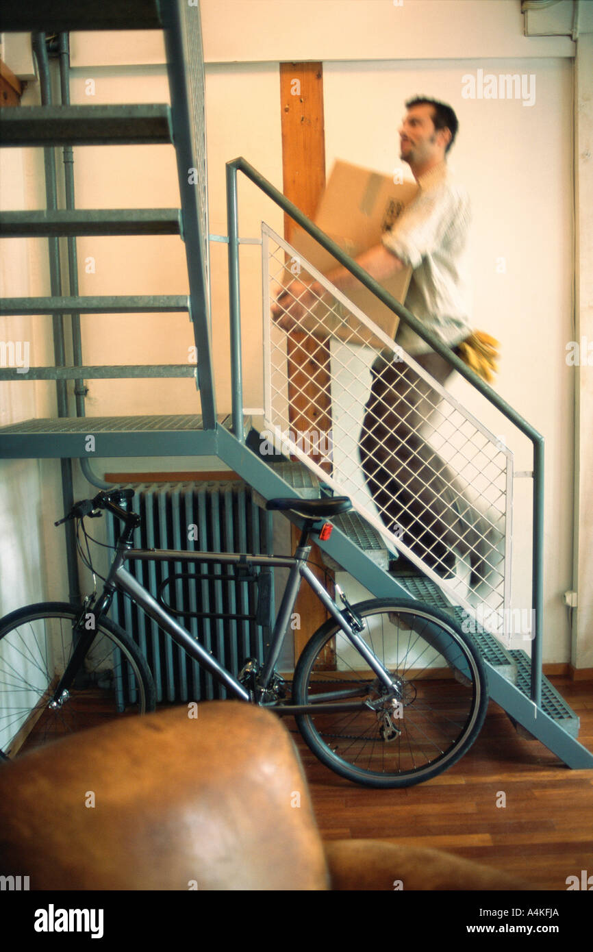 El hombre lleva caja escaleras Imagen De Stock