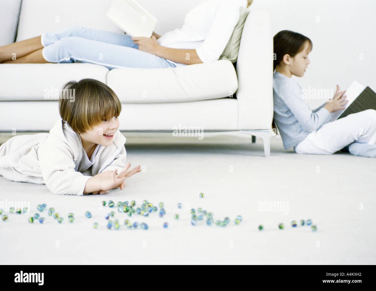 Niño jugando canicas en el suelo, la mujer y la niña leyendo en segundo plano. Foto de stock