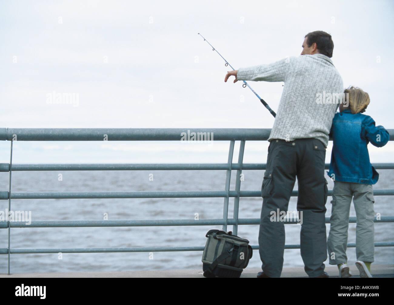 Hijo de hombre y la pesca en el muelle, el hombre apuntando, longitud completa Imagen De Stock