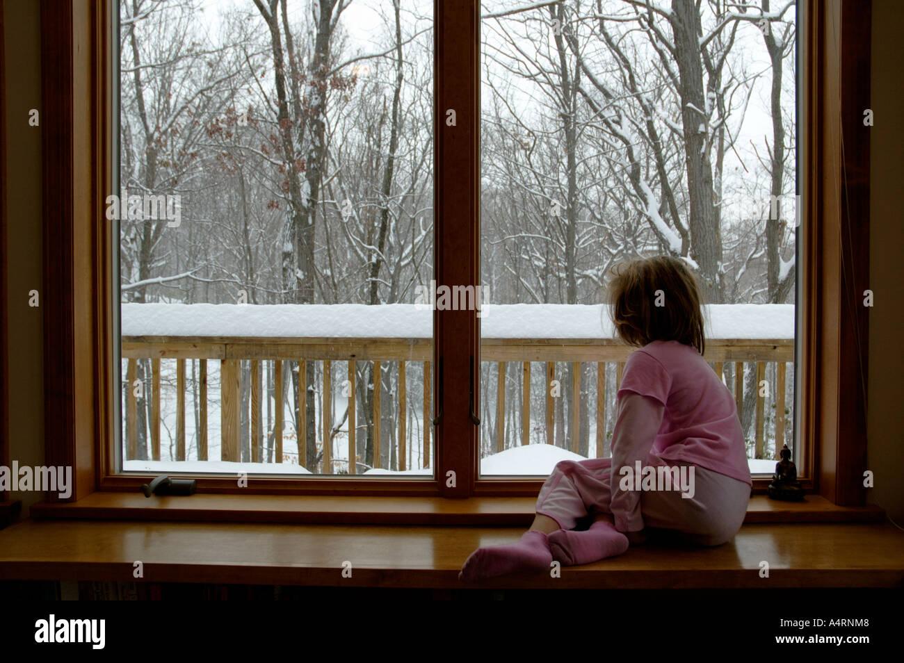 Solitario joven niña mira por la ventana en un día de nieve gris Imagen De Stock