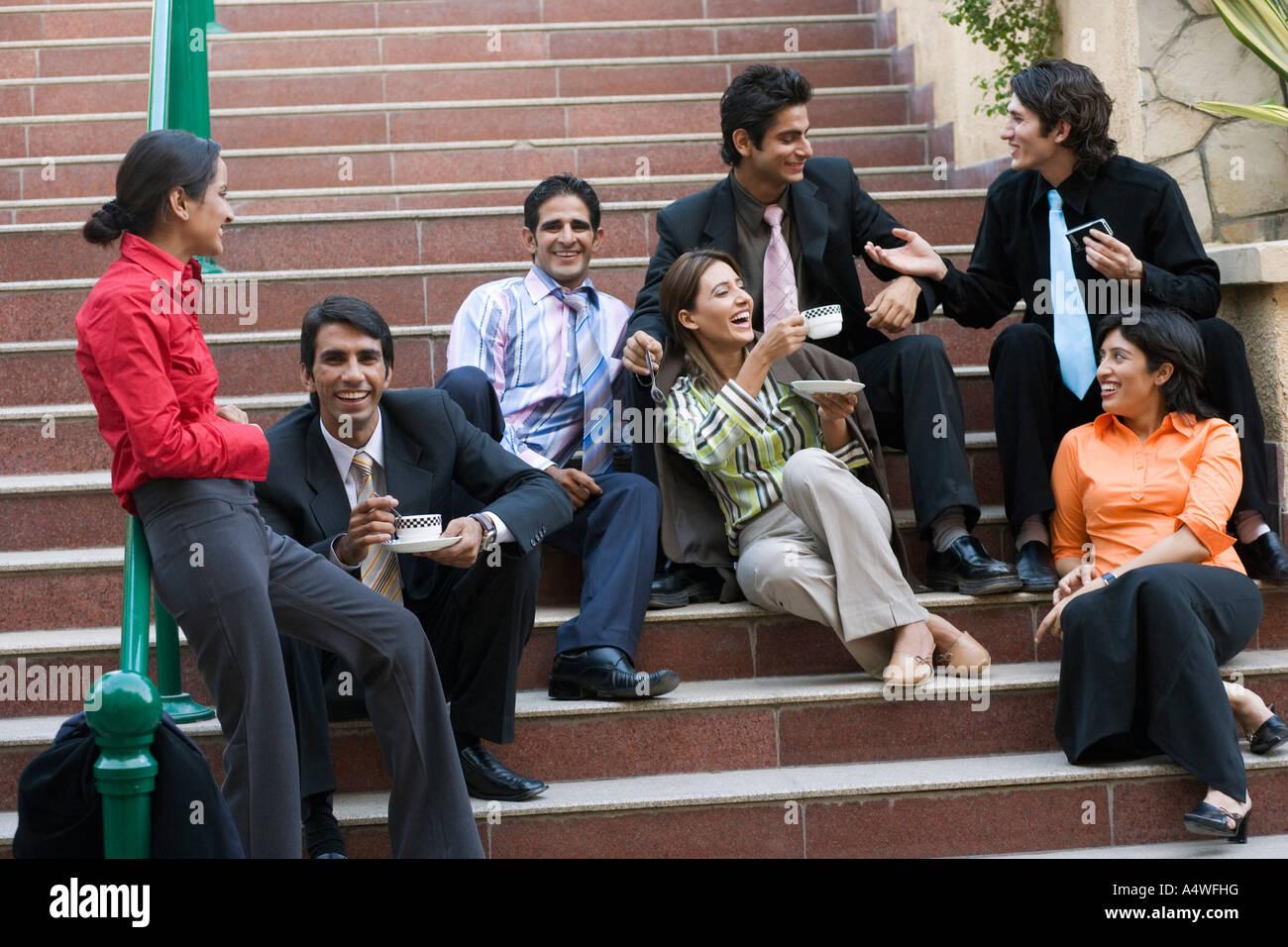 Empresarios relajándose en caja de escalera exterior Imagen De Stock