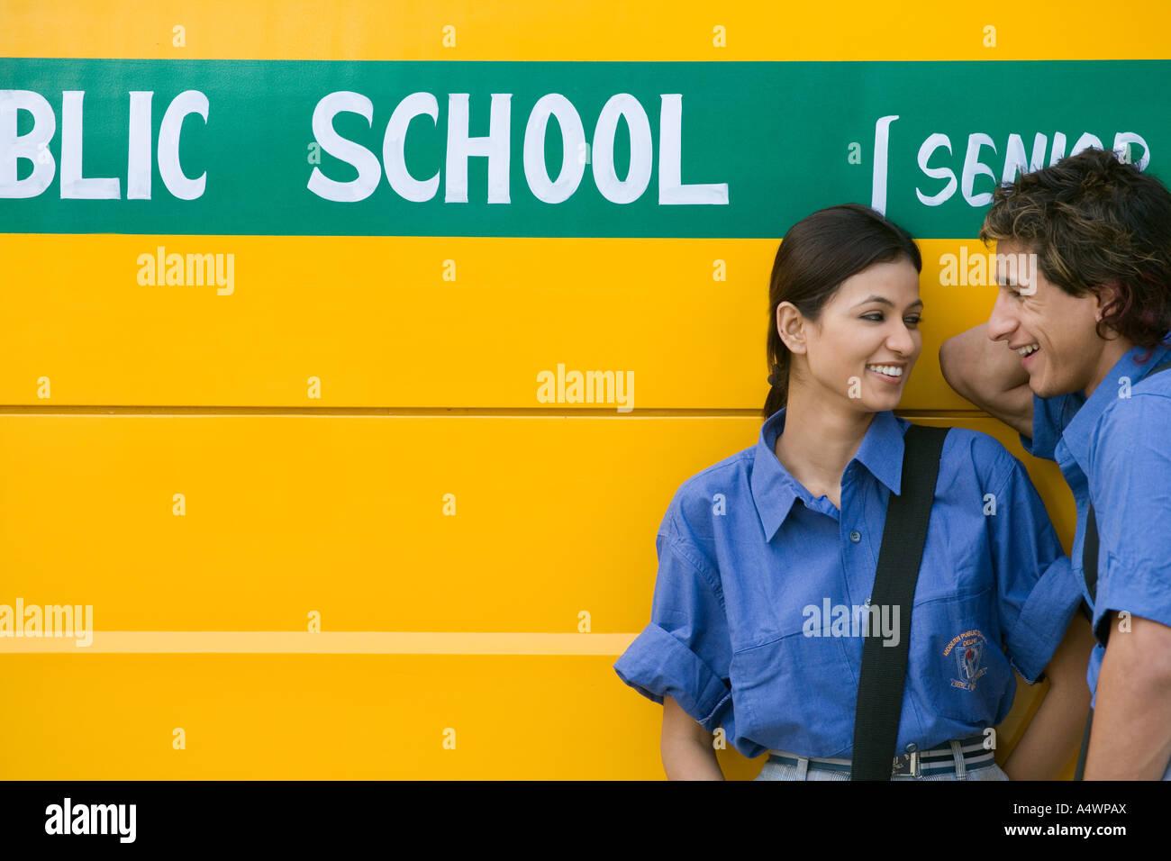 Pareja estudiante riendo delante del autobús escolar Imagen De Stock
