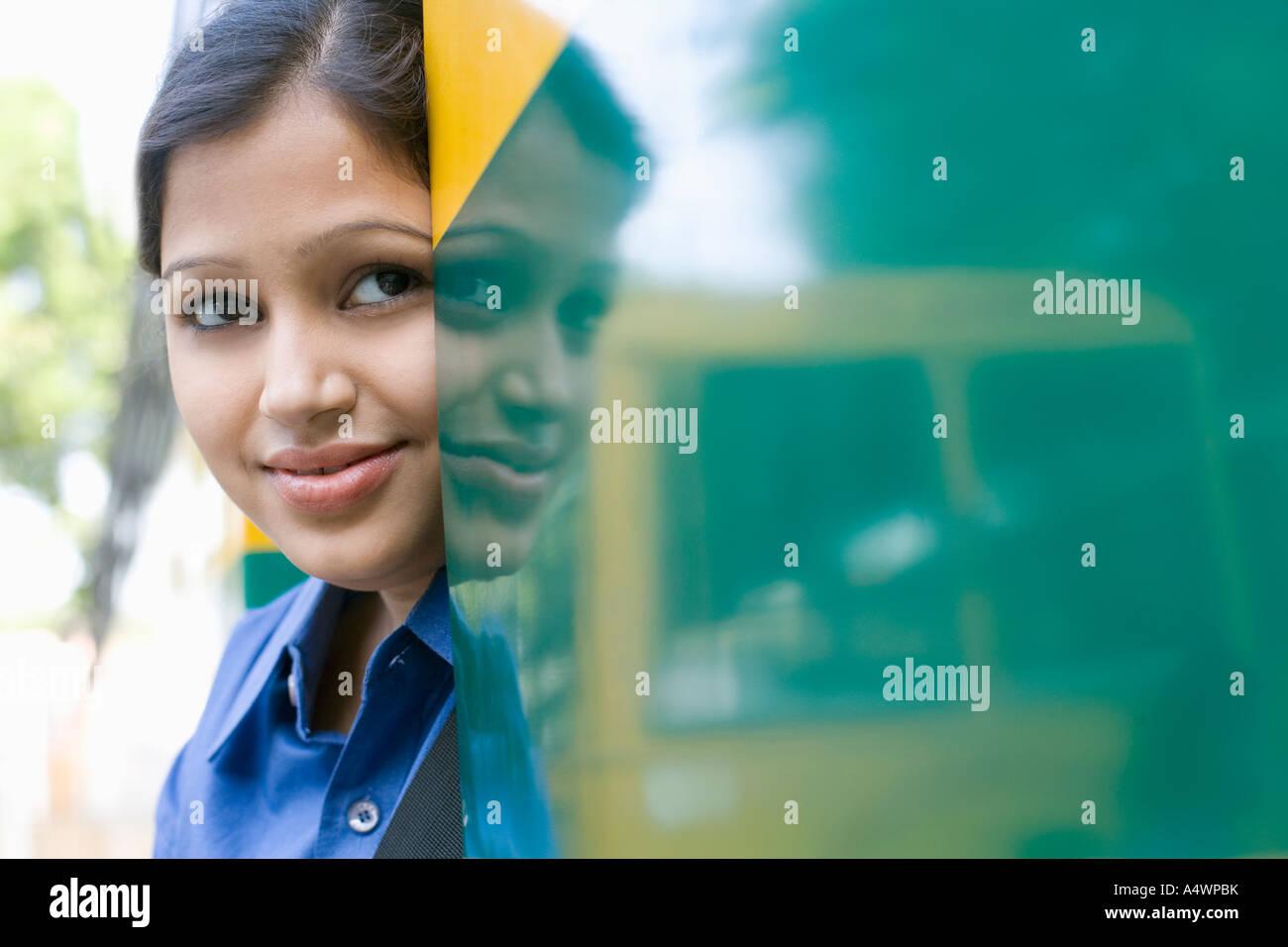 Estudiante de pie en la puerta del autobús escolar Imagen De Stock
