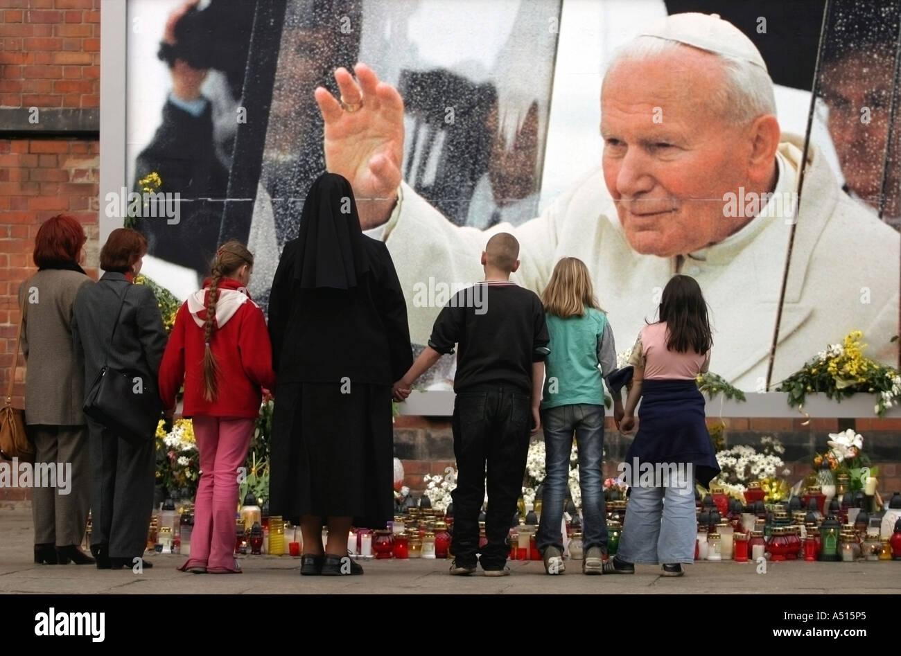 Un grupo de personas se unió a manos acompañado por un religioso cristiano mira las velas en memoria de Juan Pablo II Imagen De Stock