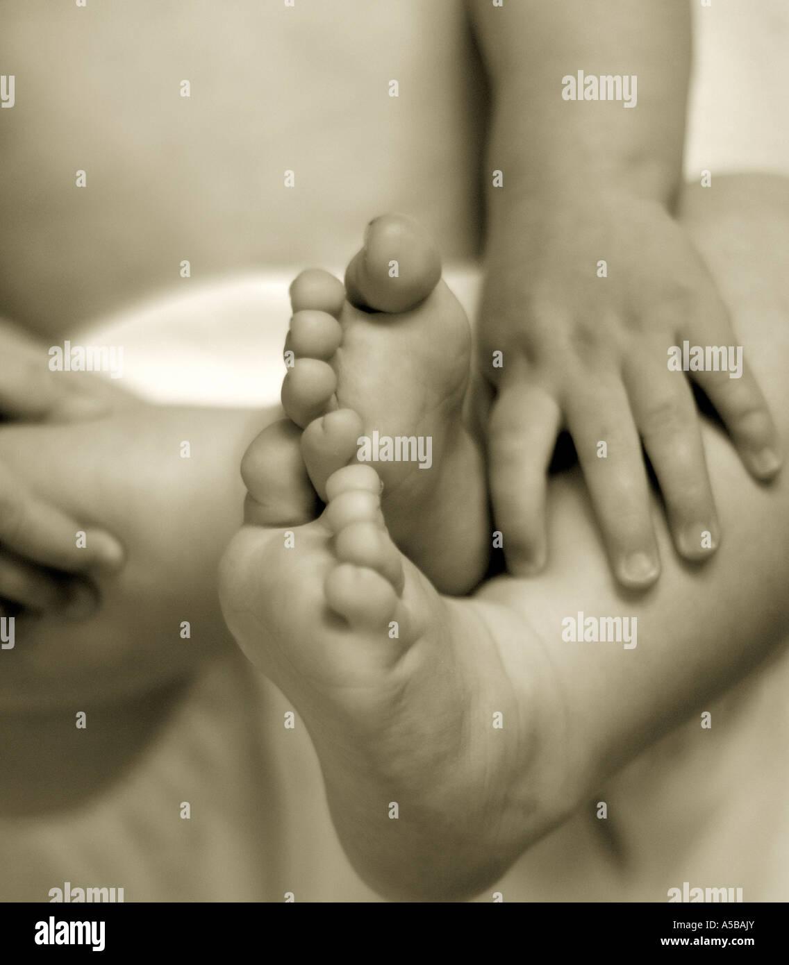 El bebé lactante holding y descubriendo las manos y los pies. Imagen De Stock