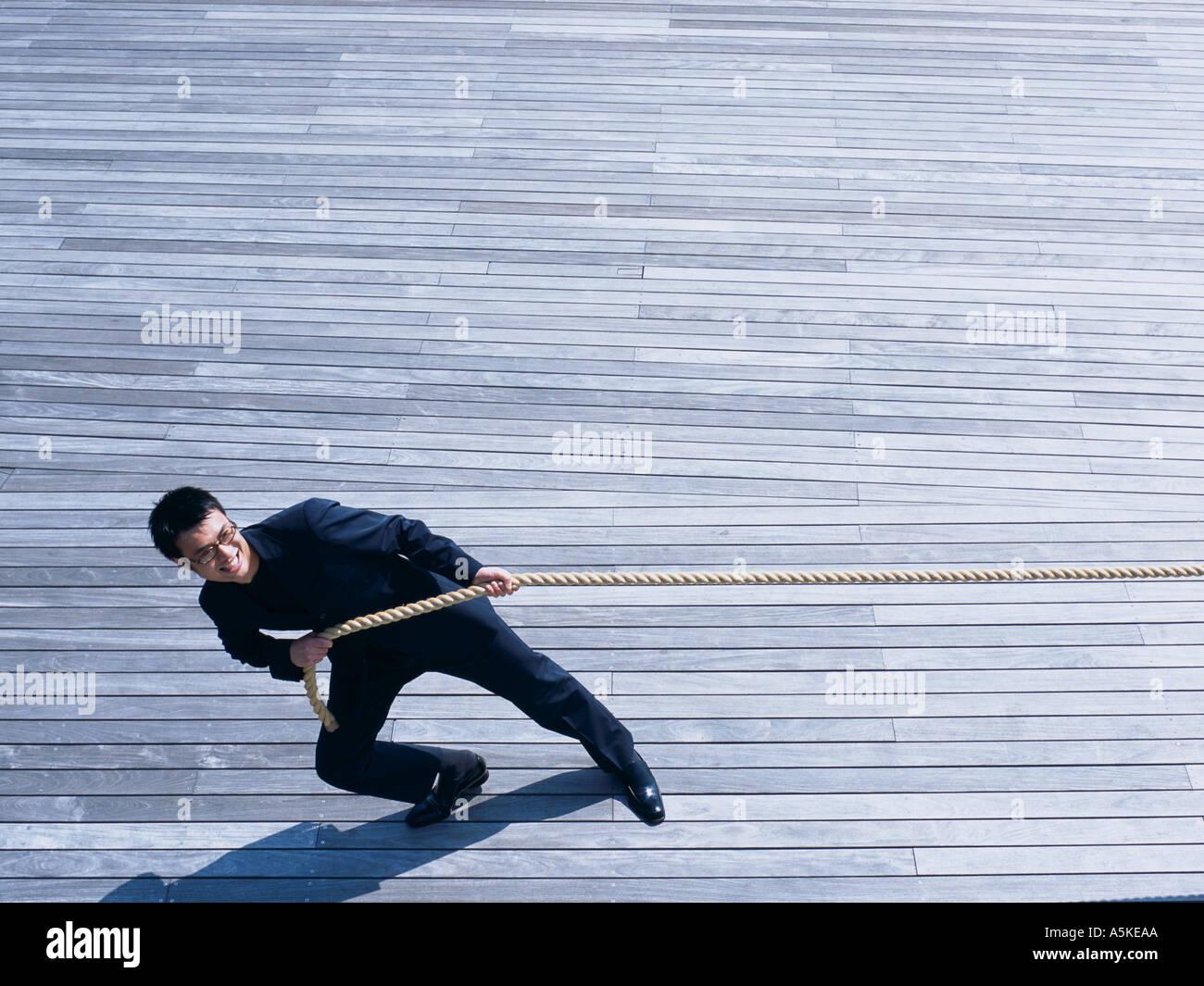 Hombre asiático tirando de una cuerda Imagen De Stock