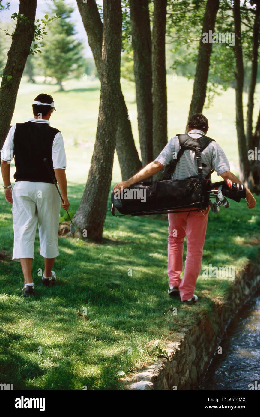 Los golfistas buscando bola bajo los árboles, vista trasera Foto de stock