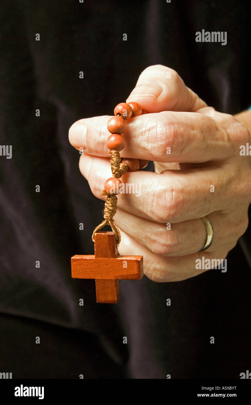 La mano que sostiene una mujer sola década mientras rezan el rosario Imagen De Stock