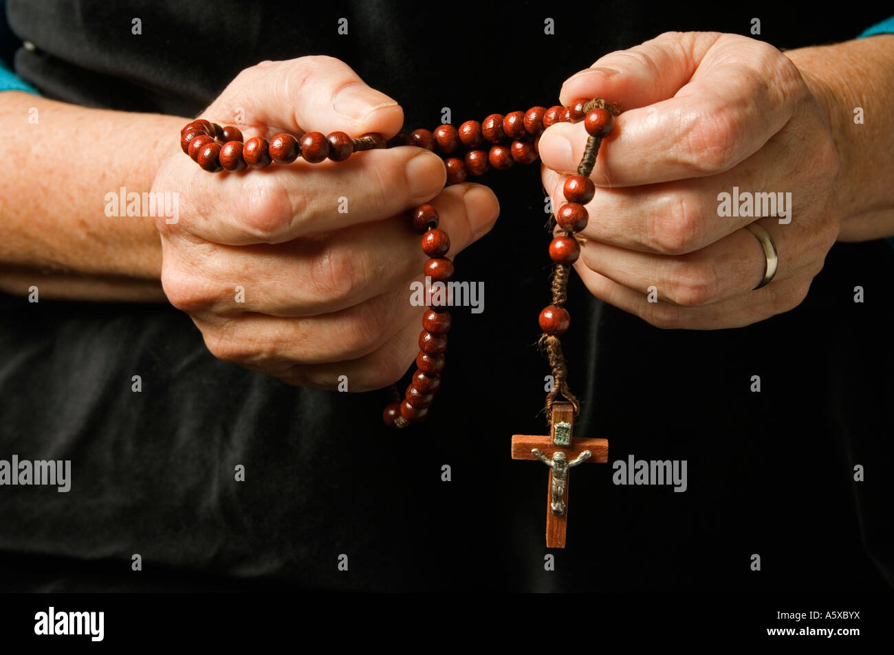 La mano que sostiene una mujer mientras rezan el rosario Imagen De Stock