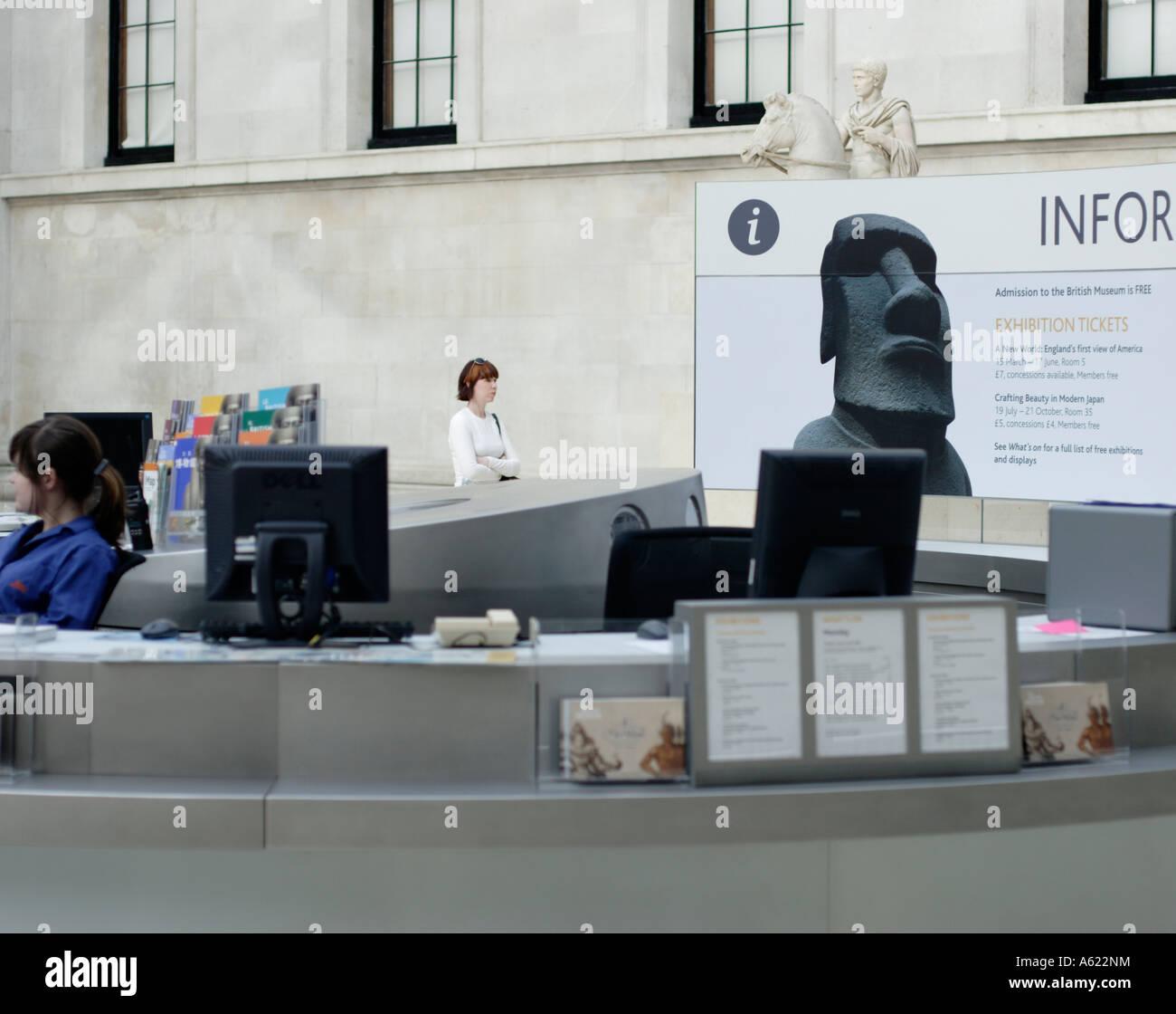 Empleado de mostrador de información y en el Museo Británico de Londres con una mujer visitante y estatua ecuestre romana Foto de stock