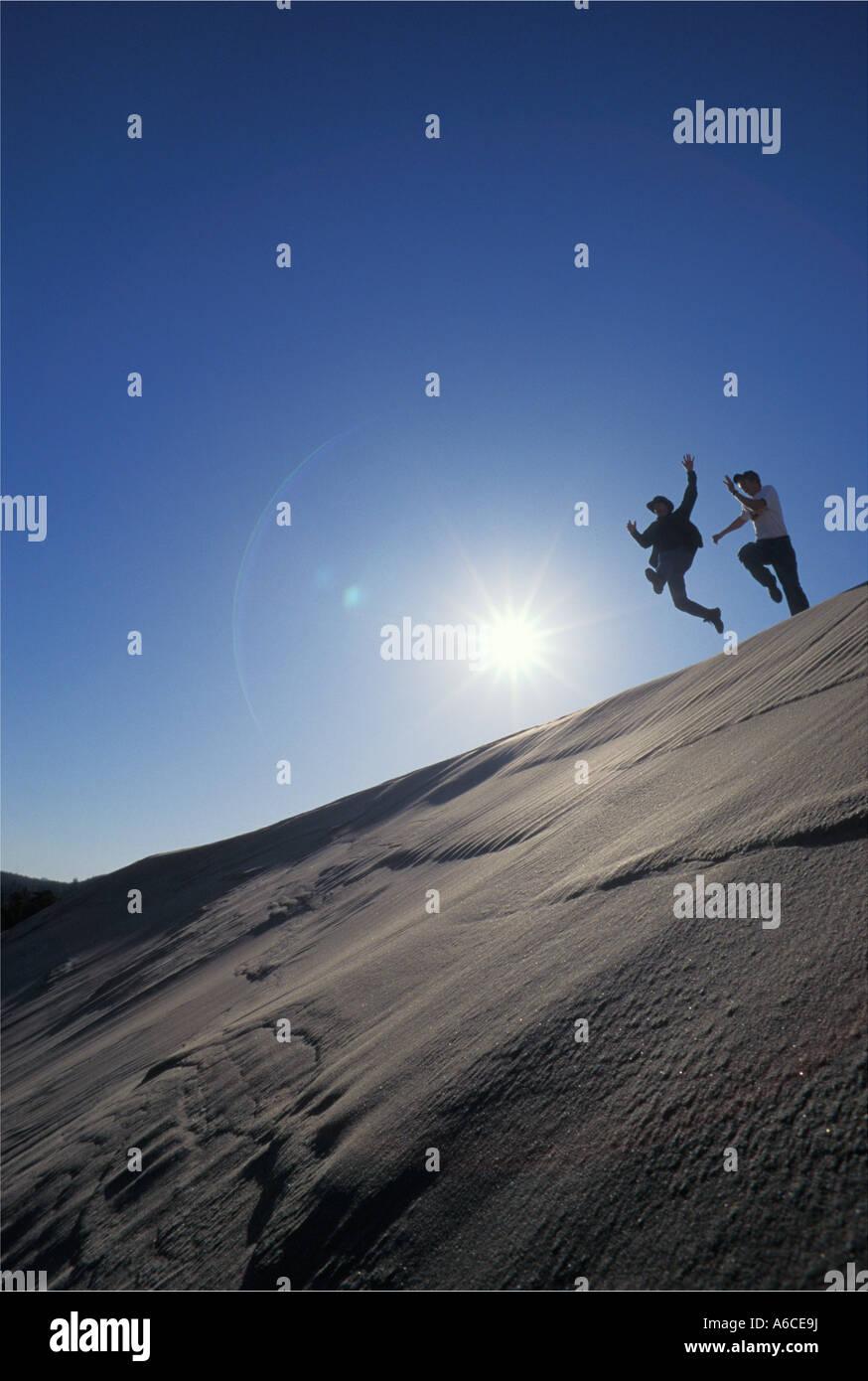 Dos hombres jóvenes saltando de una duna de arena ridge Umpqua Dunes Oregon Dunes National Recreation Area Oregon Foto de stock