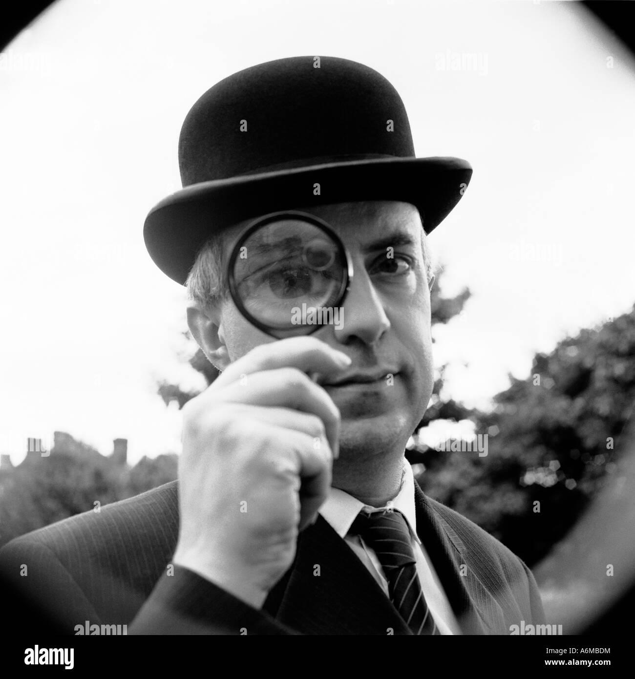 Hombre mirando a través de una lupa Imagen De Stock