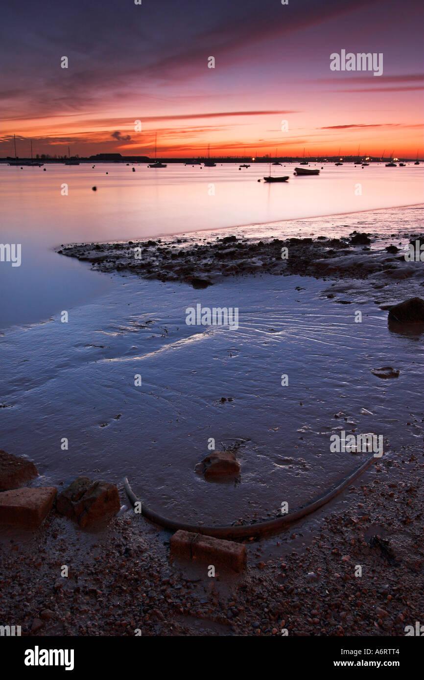 Un hermoso crepúsculo en Burnham en Crouch en Essex. Marea baja sobre el río Crouch revela los residuos atrapados en el lodo. Imagen De Stock
