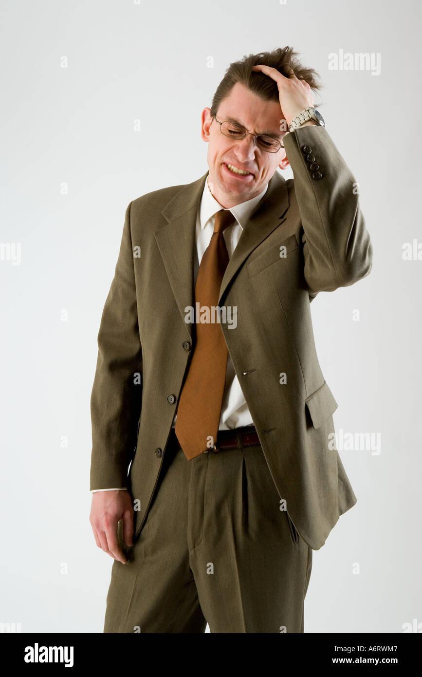 Hombre de negocios vistiendo un traje marrón de manos en el cabello  frustrado f7fde2809f1