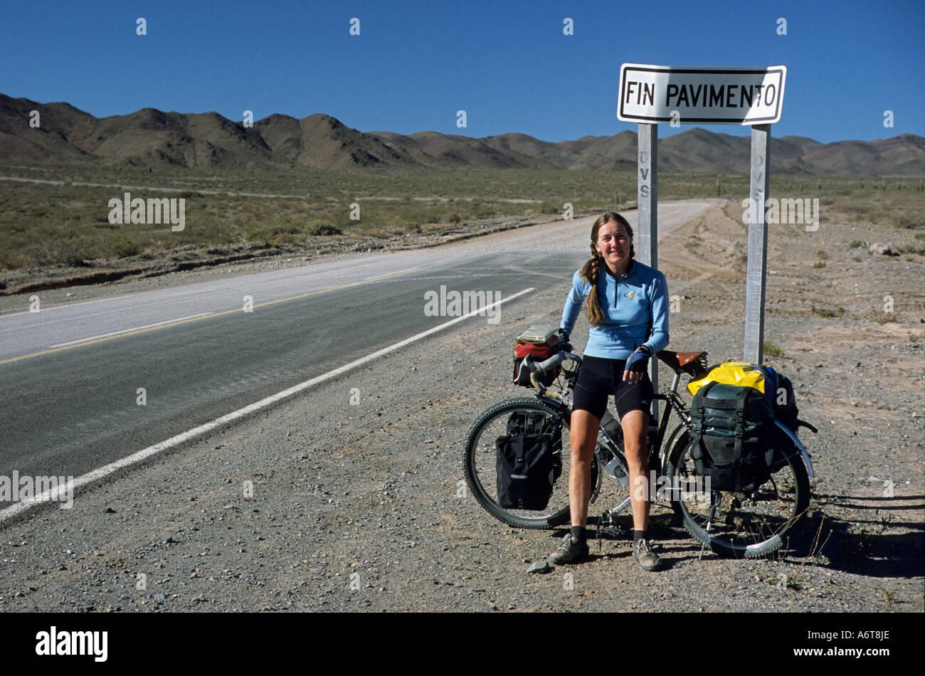 Ciclista femenina mirando con bicicleta junto a fin Pavimento firmar el final de la carretera en el norte de Argentina a distancia Imagen De Stock