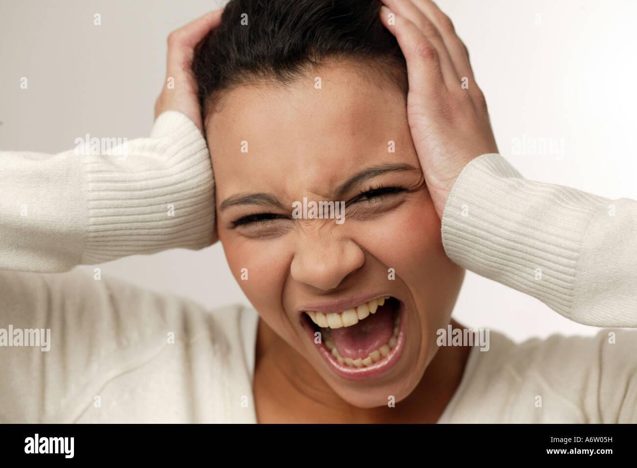 Gritando joven sosteniendo su cabeza con sus manos Foto de stock