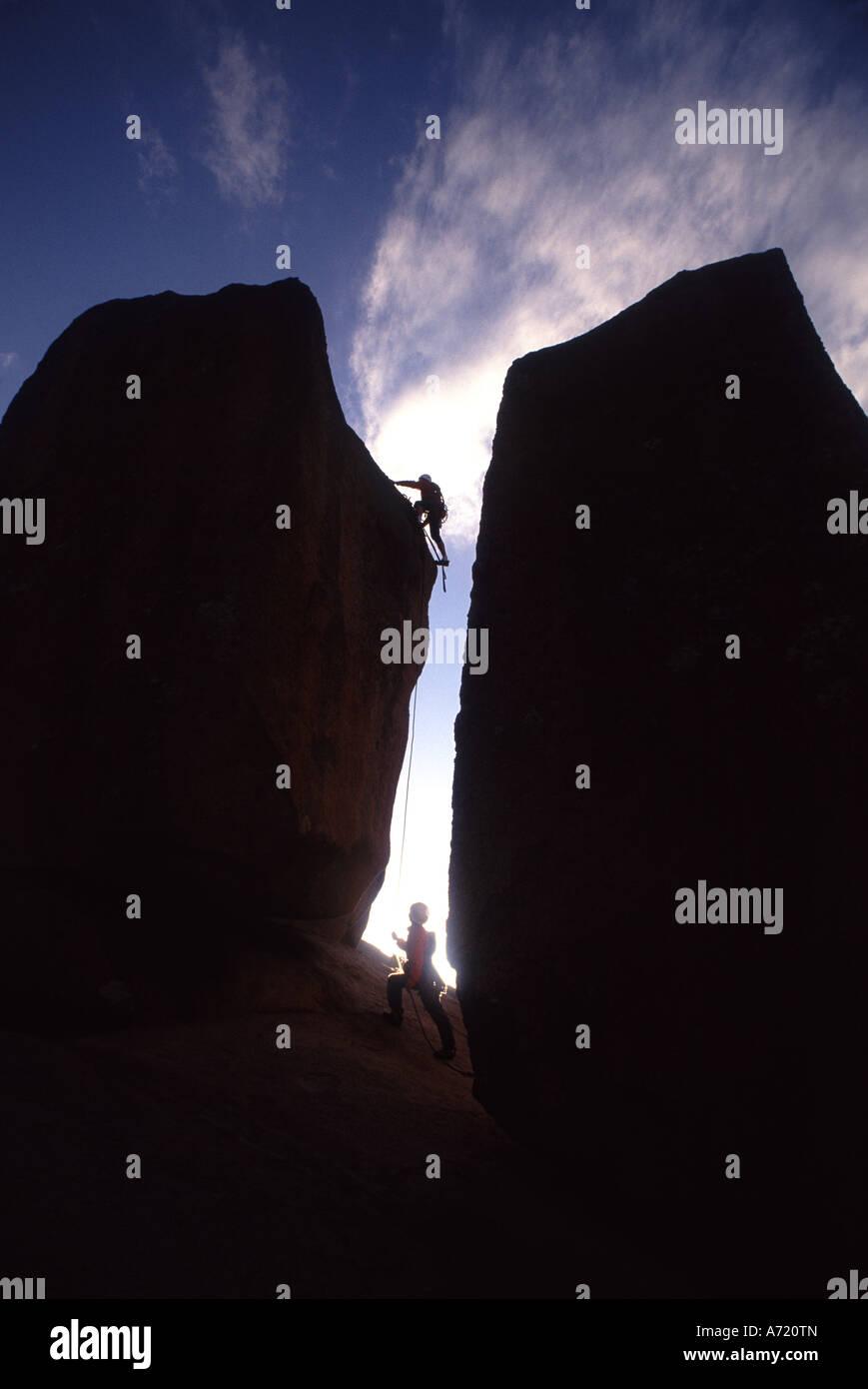 La silueta de dos hombres pueden verse escalada Imagen De Stock