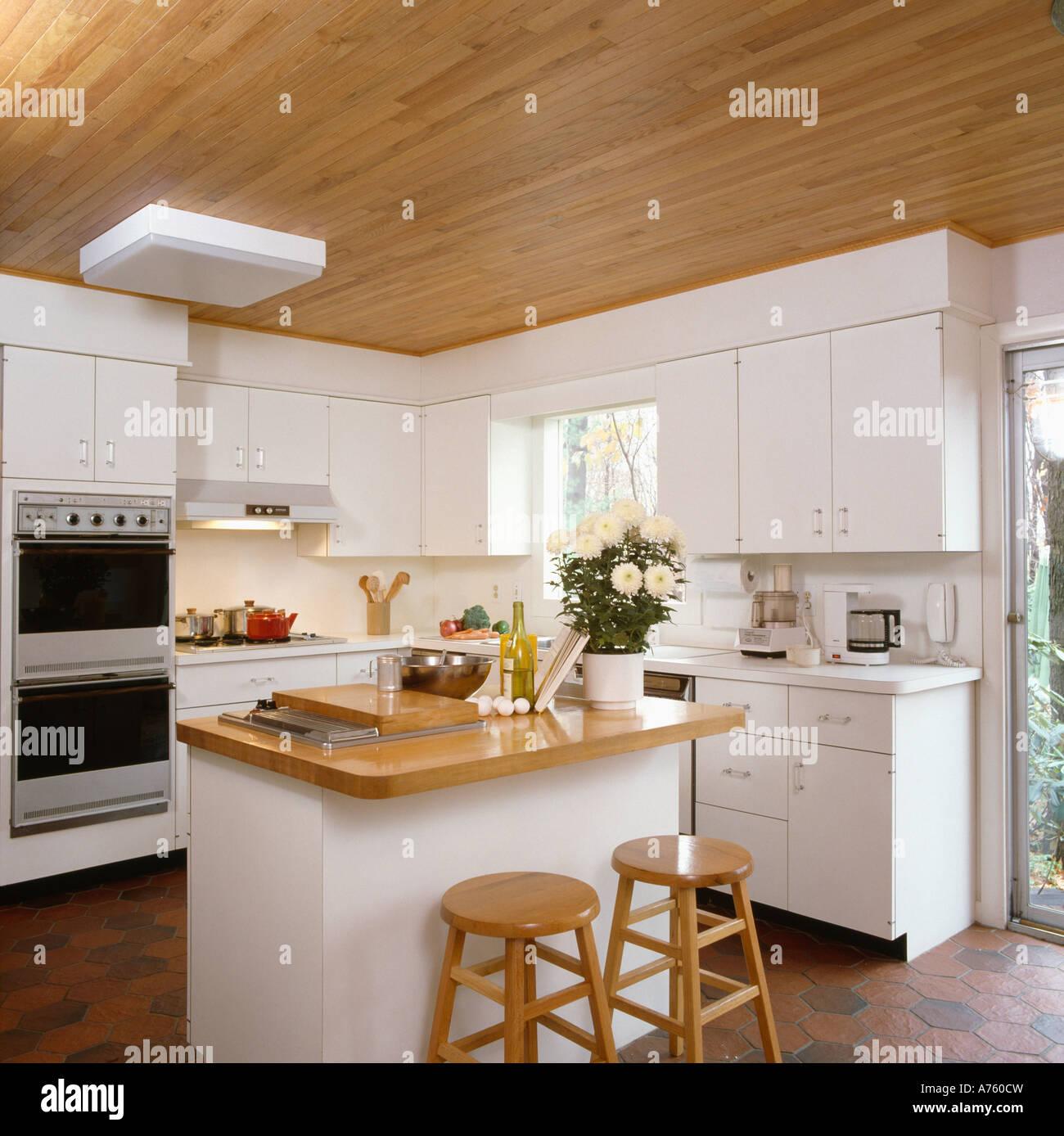 Techo de madera en la moderna cocina con isla unidad blanca