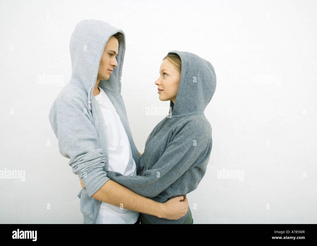 Pareja joven vistiendo sudaderas con capucha, sosteniendo cada otros alrededor de la cintura, cara a cara. Imagen De Stock