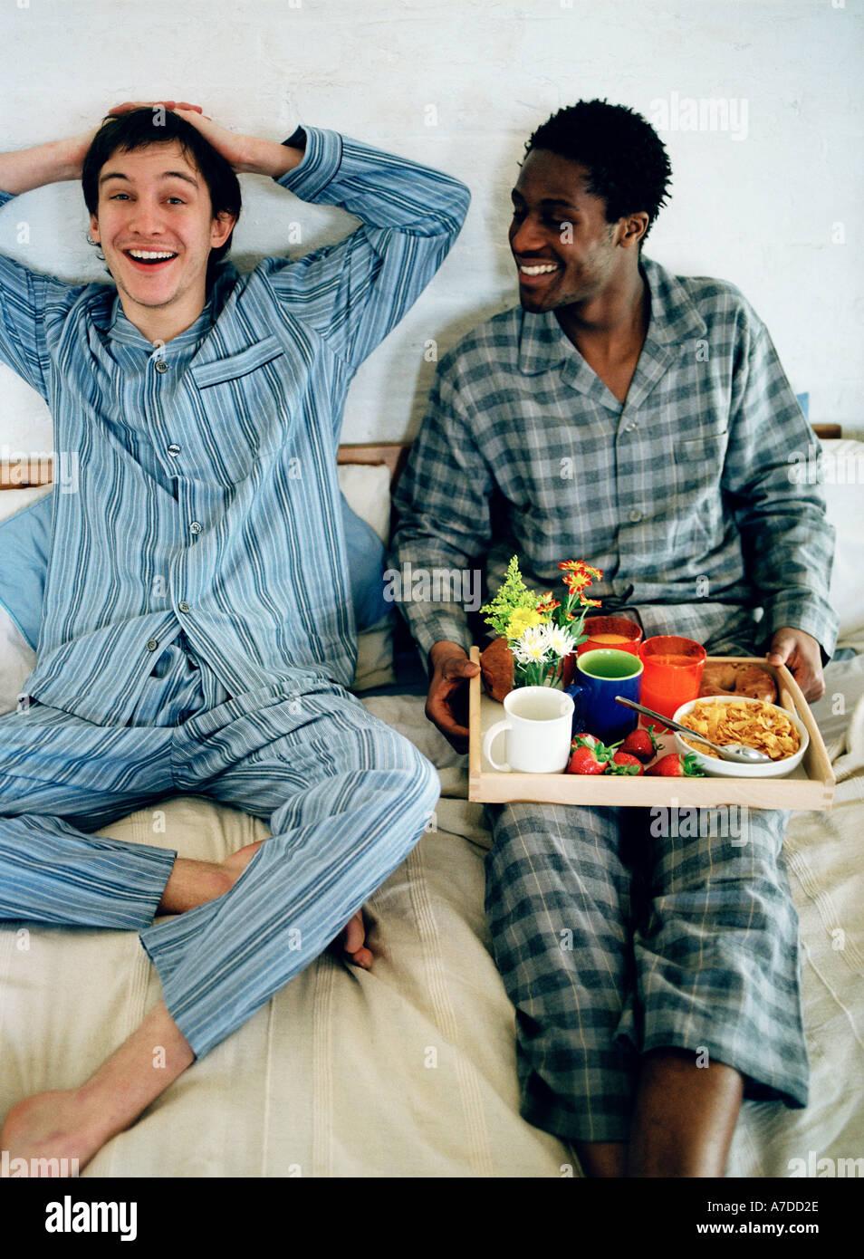 Feliz blanco negro amigos desayunando en la cama Imagen De Stock