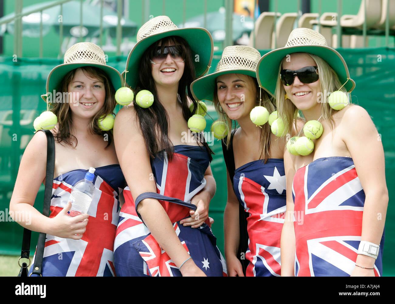 Cuatro jóvenes patrióticos a los aficionados al tenis femenino portando la bandera australiana. Foto de stock