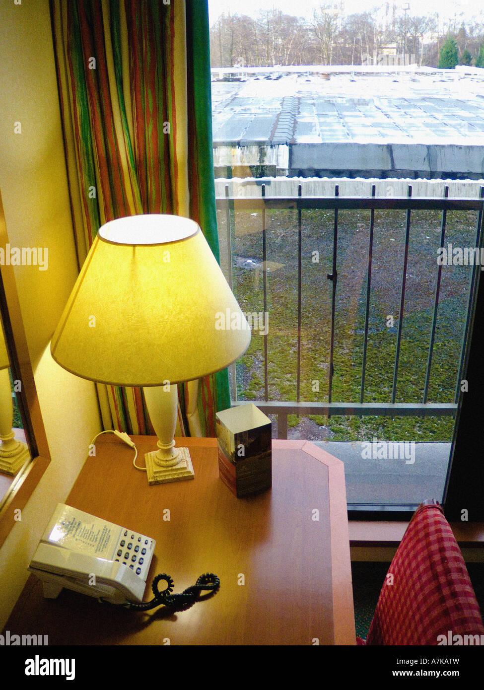 Escritorio con teléfono y lámpara en uk hotel aburrido aburrido ver fuera de la ventana en segundo plano. Imagen De Stock