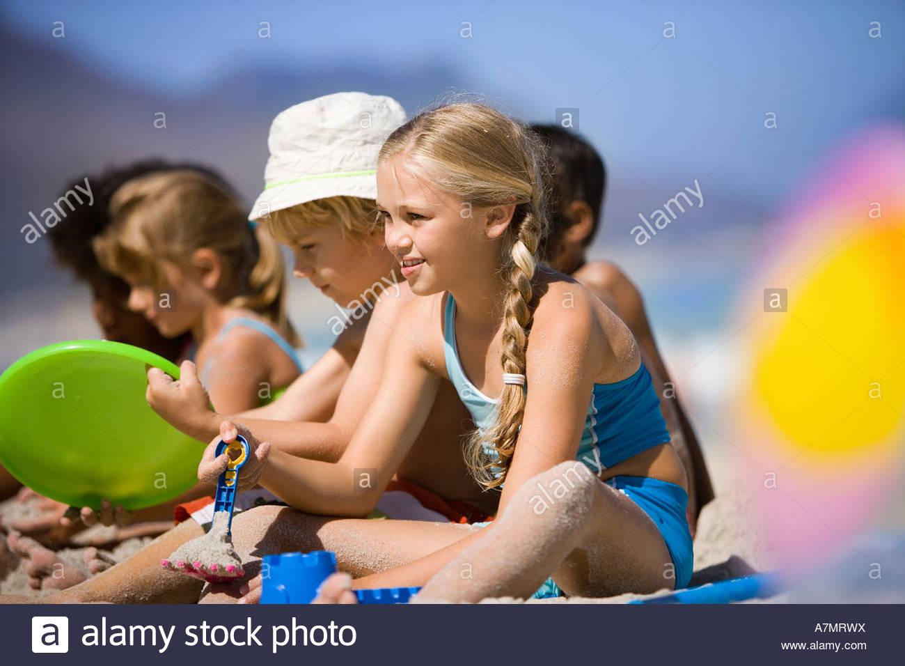 4 9 niños sentados en línea en Playa Vista lateral sonriente enfoque diferencial Imagen De Stock