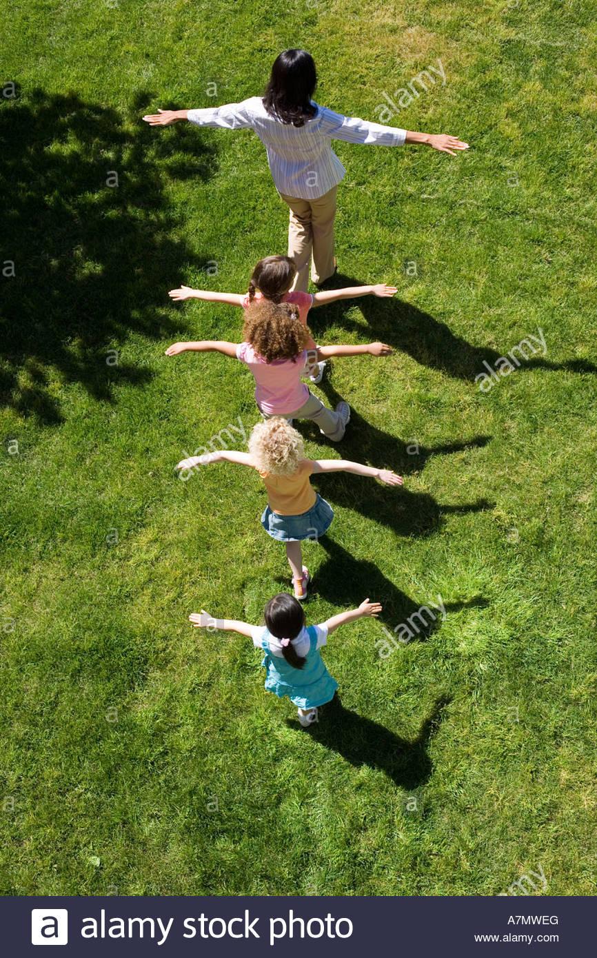 Los niños de 3 a 5 siguientes maestro en línea sobre la hierba los brazos extendidos vista aérea Imagen De Stock
