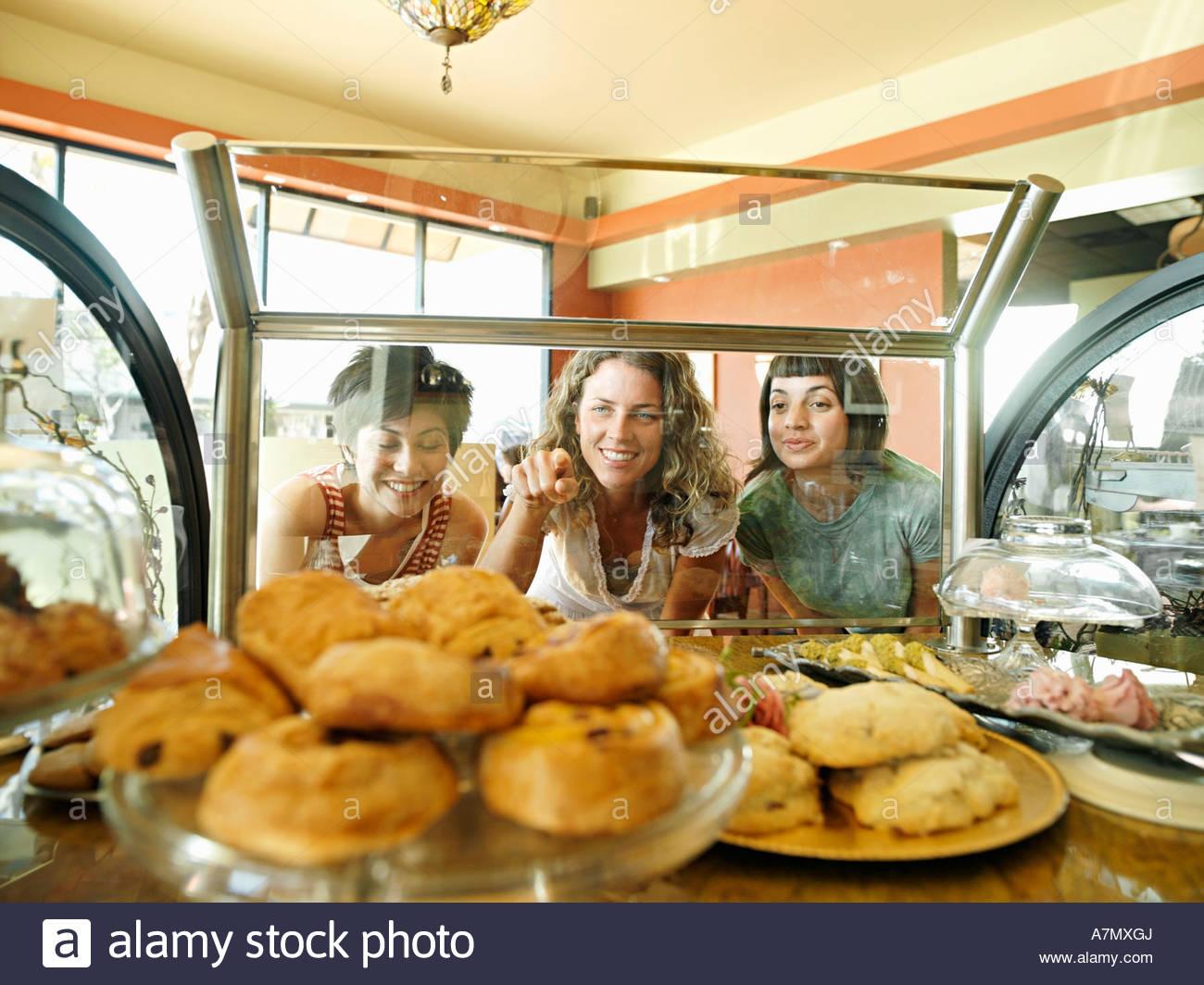 Tres jóvenes mujeres mirando a pasteles en la pantalla en el café una mujer señalando ver a través Imagen De Stock