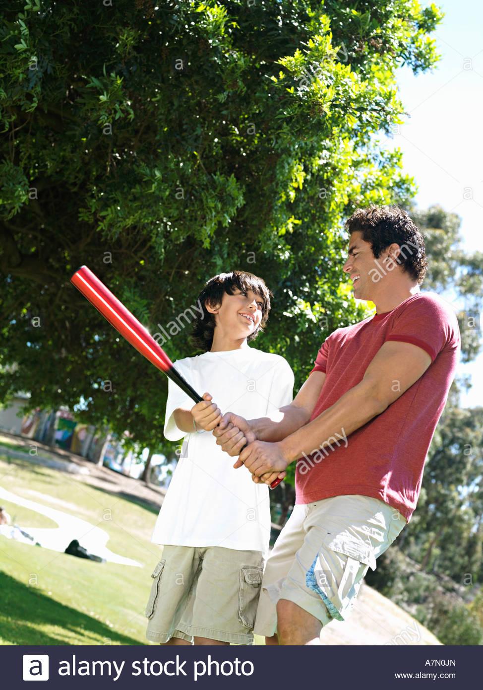 Padre hijo de enseñanza 10 12 cómo mantener bate de béisbol de pie sobre el césped en el parque Imagen De Stock