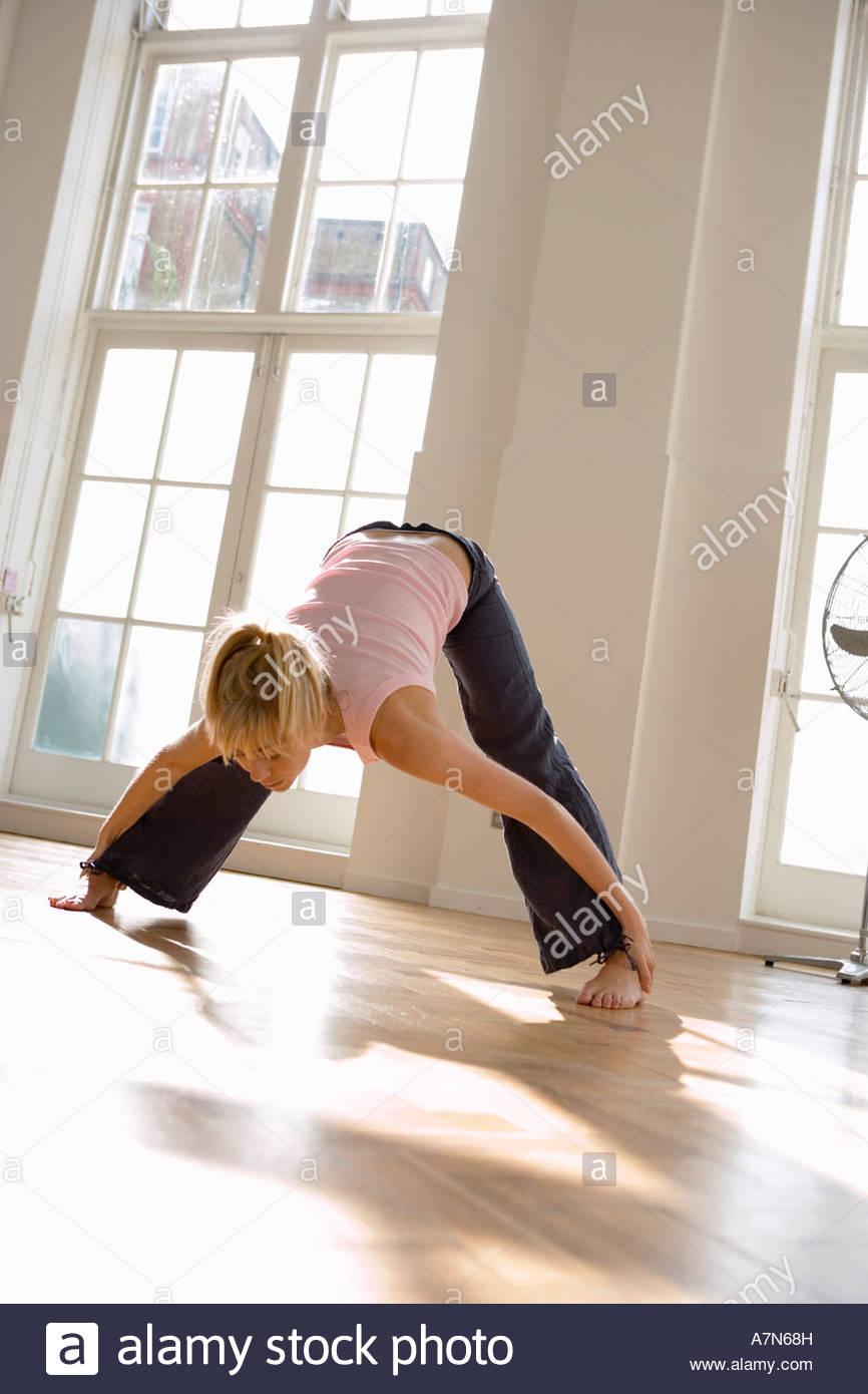 Mujer el ejercicio de tocar los dedos de los pies con piernas separadas vista frontal de la inclinación de Imagen De Stock