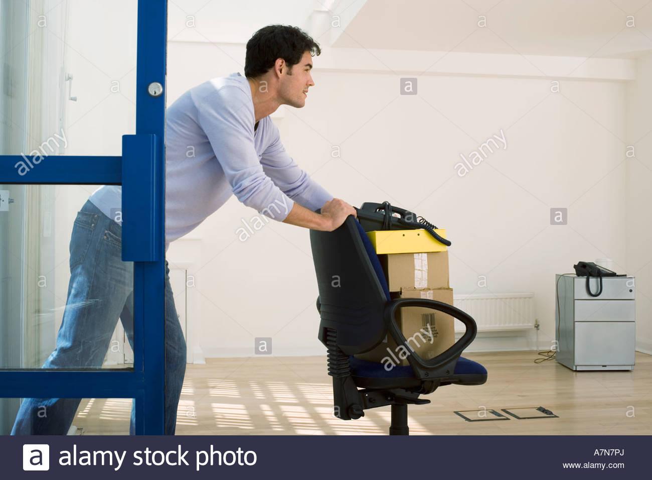 Empresario en jeans con silla de oficina para mover las cajas en la oficina vacía perfil sonriente Imagen De Stock