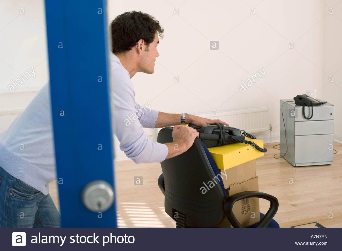 Empresario con silla de oficina para mover las cajas en la oficina vacía vista lateral Imagen De Stock