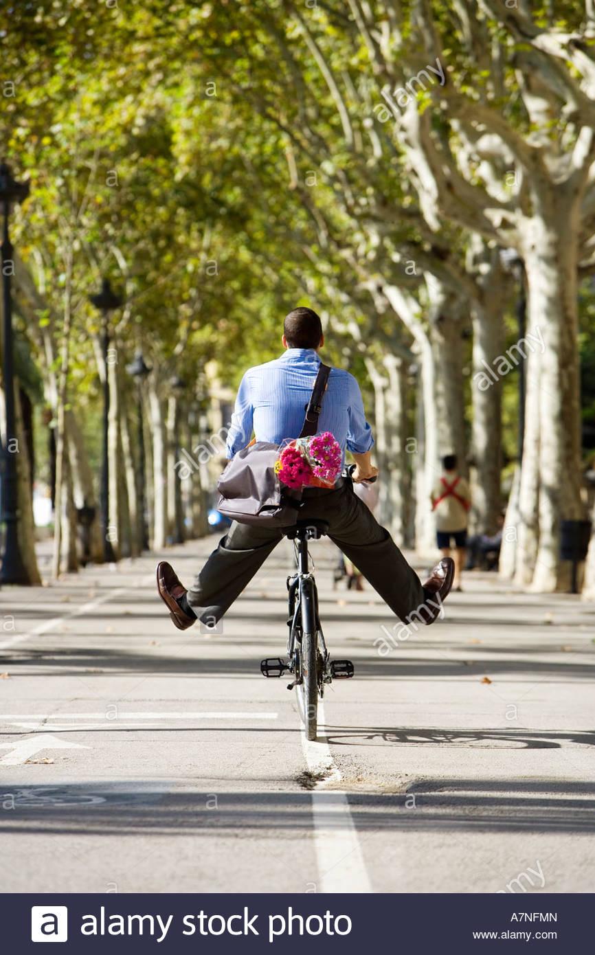 Hombre en bicicleta Ruta arboladas con piernas, bolsa de transporte y ramo de flores de color rosa vista trasera Imagen De Stock