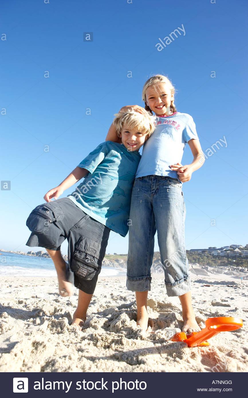 Niño y niña de 6 8 7 9 pie en playa chica sonriente niño recostado en ángulo de visión Imagen De Stock