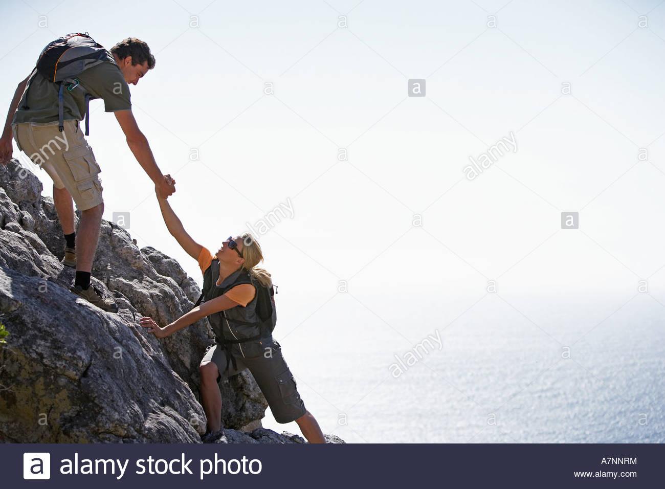 Par de escalada con luz solar brillante hombre ayuda a la mujer en el fondo del mar vista lateral Imagen De Stock
